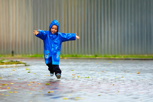 Мальчик с радостью бегает под дождем